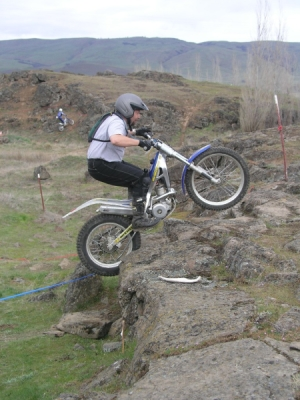 riding a trials bike up a rock face.